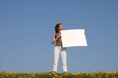 Pretty girl in dandelion field holding blank banner with copy space. photo