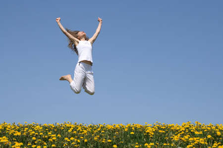 Smiling young woman in a happy jump in flowering spring field.