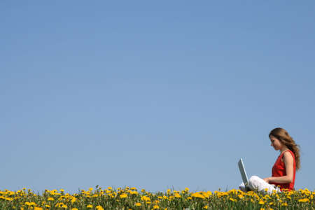 distant work: Girl working with laptop outdoors in a flowering spring field. Stock Photo