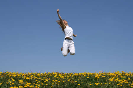 I love life! Smiling girl in a happy jump.