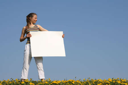 Nice girl in a flowering field, holding blank white cardboard with copy space. photo