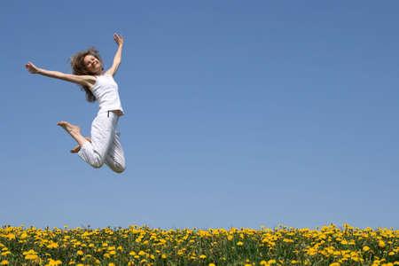 dandelion field: Smiling pretty woman in a beautiful jump. Stock Photo