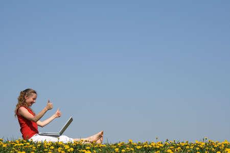엄지 위로! 꽃 필드에서 노트북과 웃는 소녀.