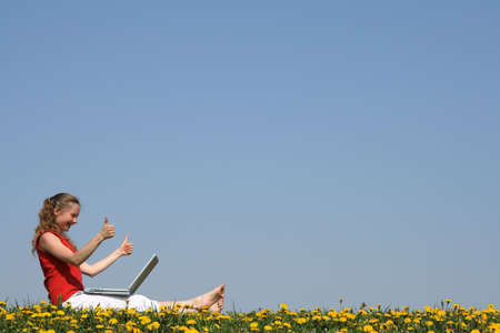 Thumbs up! Smiling girl with laptop in a flowering field. Stock Photo - 1010960
