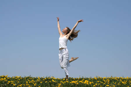 Natural beauty. Young woman in summer white clothes dancing in a flowering field. Stock Photo - 1010965