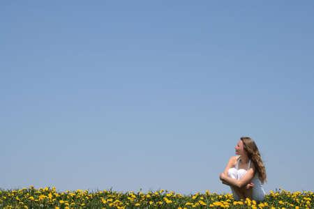 fresh air: Donna giovane che gode aria fresca e sole in un campo flowering.
