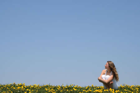 Young woman enjoying fresh air and sun in a flowering field. Stock Photo - 1010966