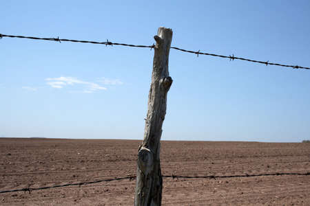 Barbed wire farm fence and cultivated farmland in spring. Stock Photo - 1067348