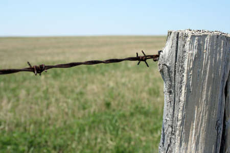 Old wooden post and barbed wire farm fence. Banco de Imagens