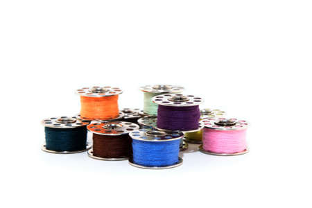 Colorful spools of thread for sewing machine, on white background.