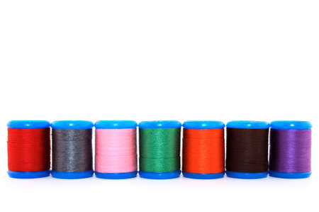 Row of colorful thread spools, on white background, with copy space. Stock Photo