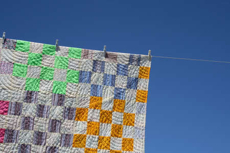 clothespegs: Laundry. Bright patchwork counterpane hanging to dry on a clothes-line.