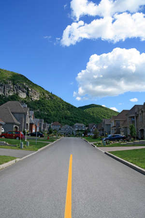 suburban: Road leading to the mountain in a prestigious suburban neighborhood. Stock Photo