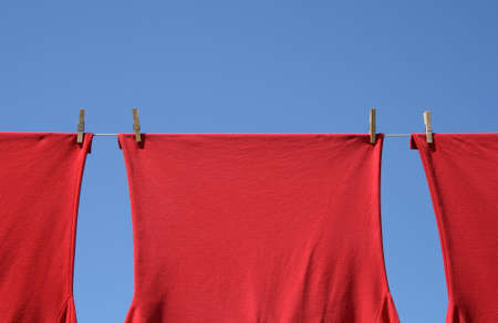 Red corporate t-shirts which hang to dry on a clothes-line.