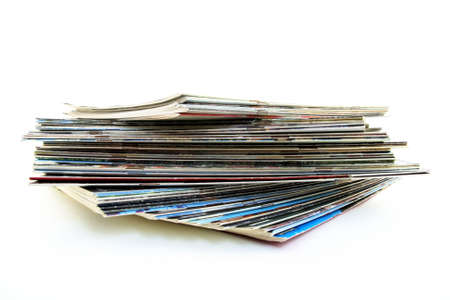 Pile of old magazines on white background.
