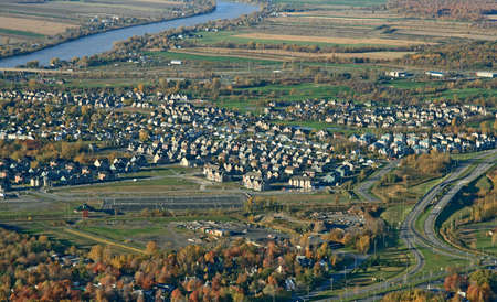 Aerial view of a suburban neighborhood and highway in bright colors of autumn. photo