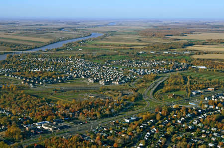 Aerial view of suburban neighborhood near highway in autumn.