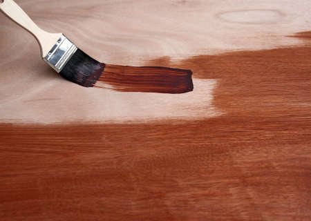 Painting a wooden surface in brown with a paint brush.