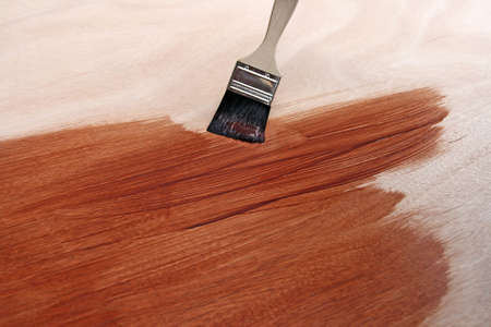 refinish: Newly painted wooden surface and paint brush. Stock Photo