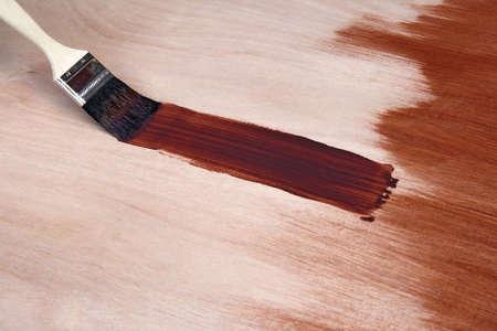 Paintbrush leaving a fresh brush stroke on wooden surface.