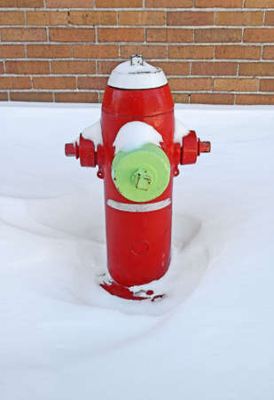 Red fire hydrant covered by snow, near a brick building. photo