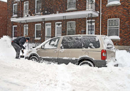 montreal: Man shovelling and removing snow from his car during a heavy snow storm. Stock Photo