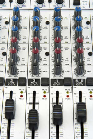 Faders and knobs of a sound mixer for audio recording.