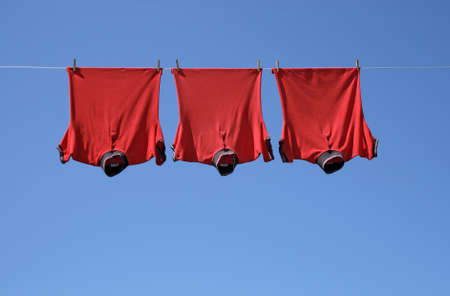 Laundry, three red t-shirts on a clothes-line.