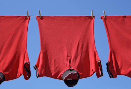 Laundry closeup, three red t-shirts on a clothes-line. Stock Photo - 2362696