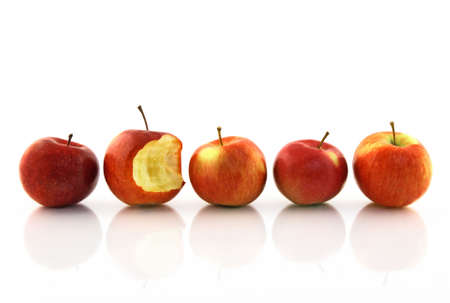 standout: One half-bitten apple among the whole red apples, reflecting on white background.