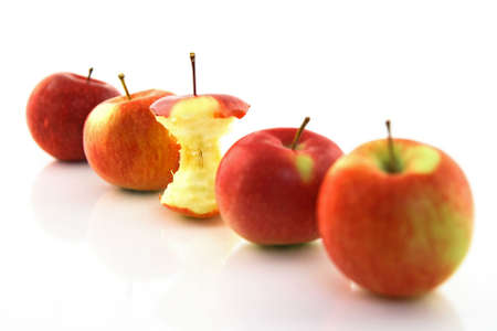 apple core: Apple core among whole apples, with focus on the core.