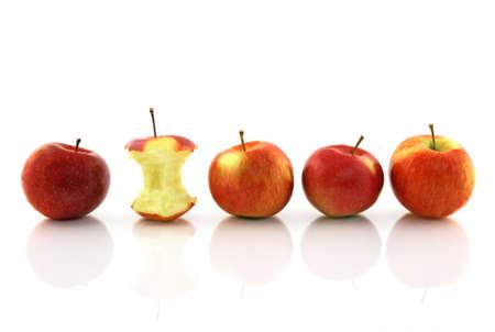 Apple core among whole apples, reflecting on white background. photo