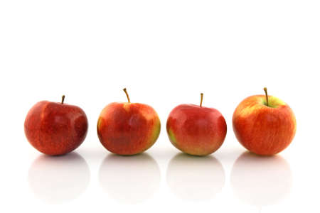 reflecting: Four red apples in a row, reflecting on white background.