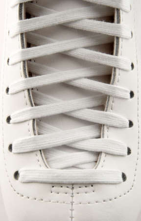 shoestring: Closeup of a figure skate, showing laces in detail.