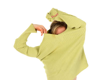 Funny girl takes off a green stylish sweater.