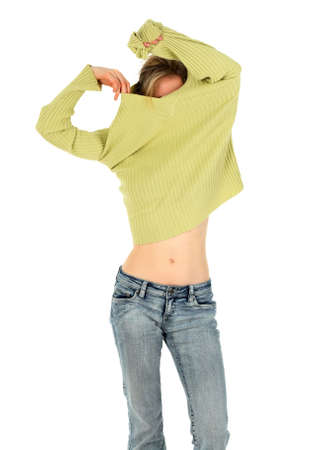 Young woman in jeans takes off a green sweater.