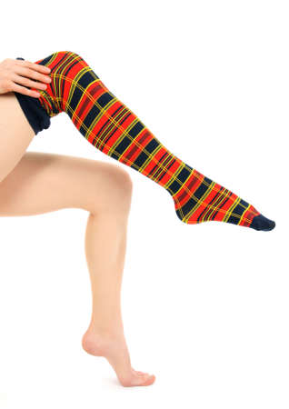 Young woman putting on bright multicolored panty-hose.