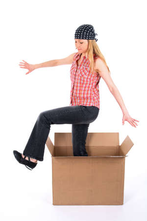 appear: Girl wearing bandanna steps out of a cardboard box. Stock Photo