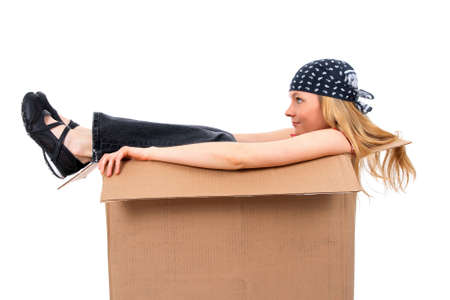 Girl sitting in a cardboard box, copy space, isolated on white. photo