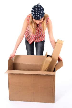 Joven mujer comprobar el contenido de una caja de cartón.  Foto de archivo