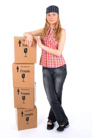 Proud young woman leaning against a stack of parcels. photo