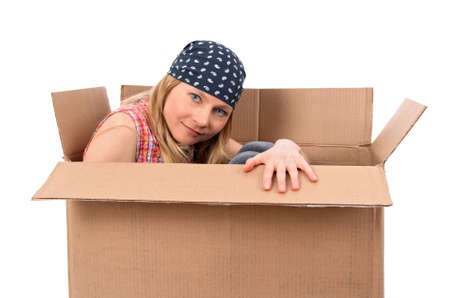Girl hiding in a cardboard box. Isolated on white. photo