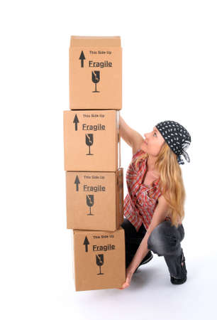 text box: Girl trying to lift a stack of heavy cardboard boxes.