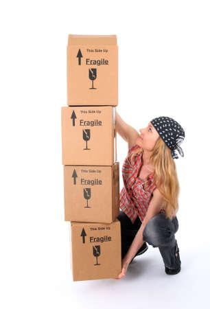 Meisje probeert op te heffen een stapel zware kartonnen dozen. Stockfoto