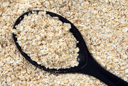Rolled oats in a black spoon. Abstract food textures.