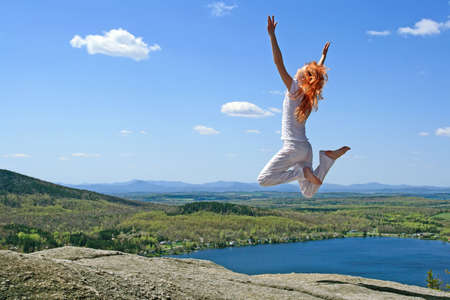 Red-haired girl jumping to the sun on the mountain. photo