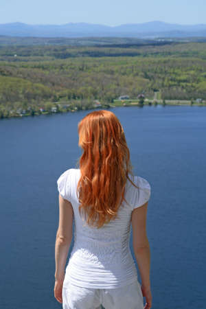 long lake: Red-haired girl looking over blue lake from the mountain.