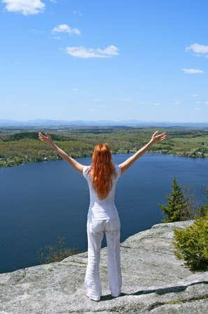 Happy woman on the mountain enjoys beautiful view. photo