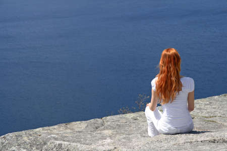 look for: Red-haired girl sitting on a rock and looking over blue water.