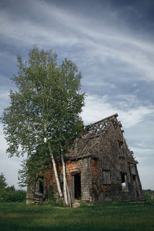 ramshackle: Spooky abandoned rural house in the field. Stock Photo